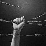 Hand behind barbed wire. With dark background Stock Images