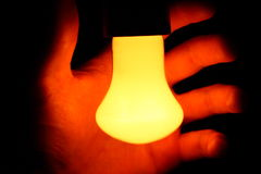 Hand behind the bulb lamp Royalty Free Stock Photo