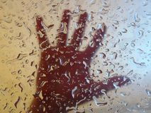 Hand behind glass with drops Stock Images