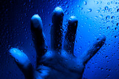 Hand behind wet window Stock Photography