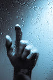 Hand behind wet window Stock Images