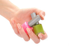 Hand with beige manicure holding two laquer Stock Photos