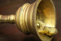 Hand bell on brown wood table Royalty Free Stock Images