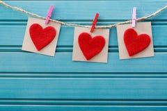 Hand-bewerkte gevoelde harten die met wasknijpers hangen Royalty-vrije Stock Foto's