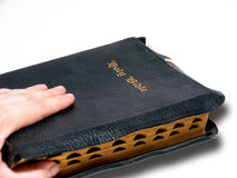 Hand and Bible. Hand on a well-worn black Bible isolated on white background stock image