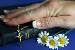 Hand on Bible. Hand resting on bible with gold crucifix and flowers Royalty Free Stock Images
