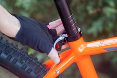 A hand in bicycle gloves lowers and raises a bicycle seat. Customize the bike. A hand in bicycle gloves lowers and raises a bicycle seat Royalty Free Stock Images