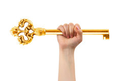 Hand and big gold key. Isolated on white background Royalty Free Stock Photos