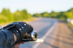 The hand of the biker on the control handle of the motorcycle and the view of the road Stock Photography