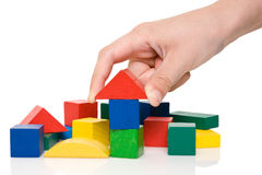 Hand bilden ein Gebäude von farbigen Blöcken. Stockbild