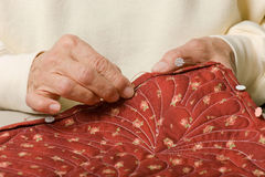 Hand binding a quilt. Stock Photo