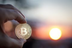 Hand with Bitcoin at sunset. Selective focus stock images