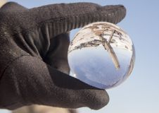 Hand holding crystal ball with lighthouses, Duluth, Minnesota. Hand with black flove holding crystal ball with reflection of shipping channel piers and Stock Images