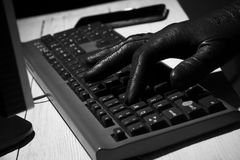 Hand in black glove types on keyboard Royalty Free Stock Photography