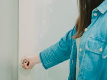 Hand of black hair woman with blue jean shirt hold on door knob. For open and entrance the door Stock Photo