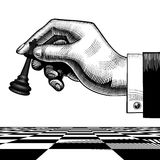 Hand with a black king chess piece Stock Images