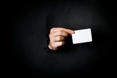 Hand through black paper Stock Photos