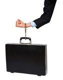 Hand in black suit with handcuffs chained to the black case Stock Photo