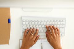 Hand of black woman type something with white wireless computer keyboard. Closeup royalty free stock image
