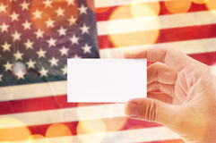 Hand with blank business card and USA flag in background. Male hand with blank business card and USA flag in background, mock up image, bokeh light effect Stock Image