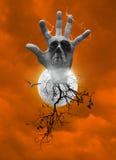 Hand blend with human skull, smoke, dead tree, bird fly, bat scream over moon and dark strom sky orange tone, Halloween concept royalty free stock photo