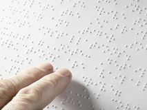 Hand of a blind person reading some braille text touching the relief. Empty copy space for Editor. Horizontal Royalty Free Stock Photography