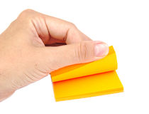 Hand with a block of yellow post it notes or Stock Image