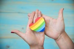 Hand on blue background holding heart rainbow stock image