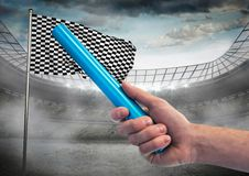 Hand with blue baton against stadium with flare and checkered flag. Digital composite of Hand with blue baton against stadium with flare and checkered flag Stock Images
