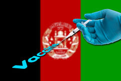 Hand in a blue glove holding syringe inject vaccine text on Afghanistan flag background royalty free stock photo