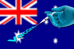 Hand in a blue glove holding syringe inject vaccine text on Australia flag background stock images