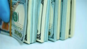 Hand in blue glove holds bundles of US dollar bundles on white surface. Closeup stock video footage