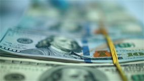 Hand in blue glove moving bundles of US dollars on white surface. Closeup stock video footage