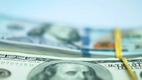 Hand in blue glove puts bundles of US dollar bundles on white surface. Closeup stock footage