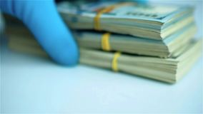 Hand in blue glove puts packs of US dollar bundles on white surface. Close up stock footage