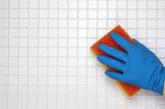 Hand in blue. Glove with red sponge on a white tile Stock Photos