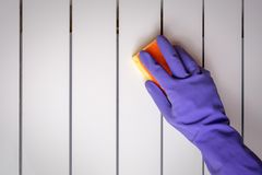 Hand blue glove wash radiator with yellow sponge. World Cleanup Day concept, copy space, close up, selective focus stock photos