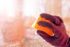 Hand blue glove washes window with yellow sponge. World Cleanup Day concept, copy space, close up, selective focus royalty free stock photos