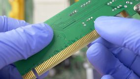 Hand in Blue Gloves Holds PCI Express Card for Computer. Hand in blue gloves holds contact system on PCI Express card for computer on electronic circuit stock video footage