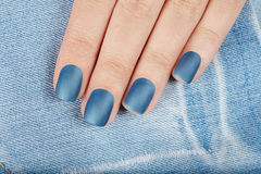 Hand with blue matte manicured nails. On jeans textile background Stock Images