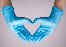 Hand in blue medical glove with Heart symbol. On white background stock photos