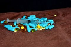 A hand in a blue medical glove holds medications and pills of different colors on a black background. The concept of pharmacologic. Al industry stock image