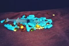 A hand in a blue medical glove holds medications and pills of different colors on a black background. The concept of pharmacologic. Al industry royalty free stock photography