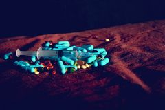 A hand in a blue medical glove holds medications and pills of different colors on a black background. The concept of pharmacologic. Al industry stock images
