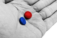 Hand with blue and red pills Royalty Free Stock Photos