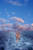 Hand in blue sea Stock Image