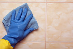 Hand in blue with yellow glove Royalty Free Stock Photos