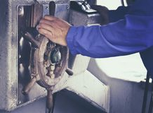 Hand on boat / marine steering wheel. Armed clothed with blue working jacket. royalty free stock images