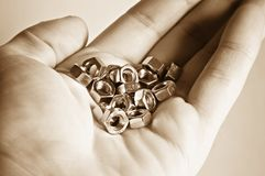 Hand with bolts and nuts Royalty Free Stock Image