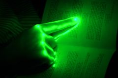 Hand on a book. Green glowing hand on a book Royalty Free Stock Photos